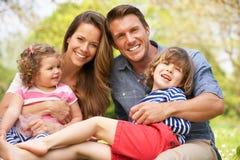 Föräldrar som sitter med barn i fält Royaltyfri Bild