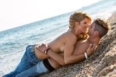 Förälskade par omkring som ska kyssas på strand. Fotografering för Bildbyråer