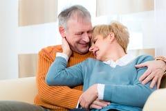 Förälskade pensionärer hemma fortfarande trots allt de år Arkivbild