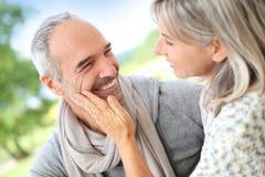 Förälskat anseende för höga par i trädgård Arkivfoton