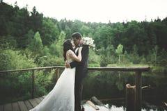 Förälskelse och passion - kyssen av gifta unga brölloppar near sjön Royaltyfria Bilder