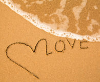 Förälskelse - skriftlig text räcker by i sand på en strand Arkivbild