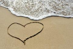 Förälskelsebegrepp - en hjärta som dras på sandstranden Arkivbild