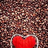 Förälskelsekaffe på valentin dag. Grillade kaffebönor med rött honom Royaltyfri Fotografi