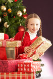 främre flicka för jul som rymmer den aktuella treen Royaltyfria Bilder