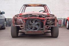 Främre sikt av den röda gamla rostiga bilen Arkivbilder