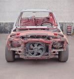 Främre sikt av den röda gamla rostiga bilen Arkivbild