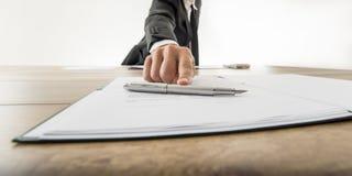 Främre sikt av en affärsman som erbjuder du ska underteckna ett dokument eller ett c Royaltyfri Foto