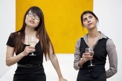 Främre sikt av unga kvinnlig med vinexponeringsglas som ser upp i konstgalleri Arkivbild