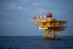 Frånlands- olja och riggplattform i solnedgång- eller soluppgångtid Konstruktion av produktionsprocessen i havet Maktenergi av vä Royaltyfri Foto