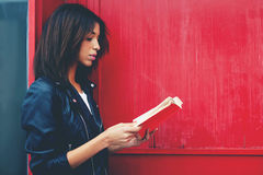 Аfro american woman read literature while standing outdoors. Young female student reading interesting book while standing in the city on red wall background Stock Photography