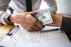 Frode disonesta in soldi illegali di affari, stretta di mano dell'uomo d'affari con soldi delle banconote del dollaro in mani da  fotografia stock