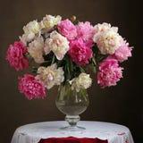 Frodig bukett av rosa pioner i en vas på tabellen Royaltyfria Bilder
