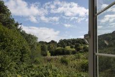 Frodig grön bygd till och med öppet fönster Royaltyfria Bilder