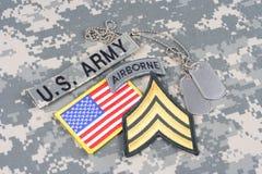 Frodig lapp för USA-ARMÉsergeant, luftburen flik, flaggalapp, med hundkapplöpningetiketter på kamouflagelikformign Royaltyfri Bild