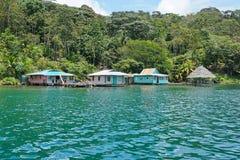 Frodig tropisk kust och lantliga hus över havet Royaltyfria Bilder