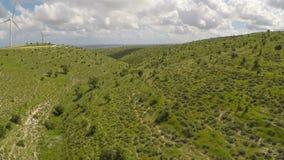 Frodigt grönt landskap med vindturbiner på kullar, utveckling för alternativ energi lager videofilmer