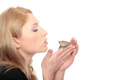 Frog. A gorgeous young blond woman kissing a frog Royalty Free Stock Images