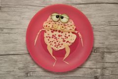 Frog compiled with cheese slices. On pink plate Stock Image