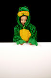 Frog Costume with Blank Sign. A little girl dressed up in a frog costume looks down at a blank sign which can display any message Royalty Free Stock Photos