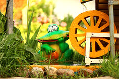 Frog figurine. Near water mill in the grass Stock Photography