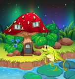 A frog jumping near the red mushroom house Stock Image