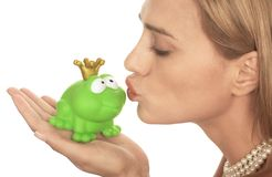 Frog prince. Being kissed by a beautiful glamour model isolated on white Royalty Free Stock Image
