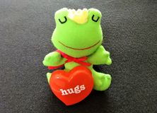 Frog prince needs love. A cute stuffed frog with a heart shaped object Stock Photos