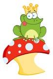 Frog prince sitting on a mushroom. Happy frog prince on a toadstool or mushroom Stock Photo