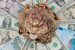 The frog is sitting on the money. The money toad on the dollar and the euro. Feng Shui Stock Photos
