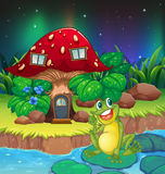 A frog sitting on a waterlily near the mushroom house Stock Photo