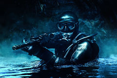 Frogman with weapons. Combat diver of special forces operations unit frogmen comes up in jungle in diving gear. Dark night, moonlight, diversionary operation royalty free stock photos