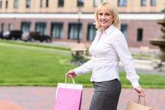Frohe ältere Dame, die mit Paketen geht Stockbilder