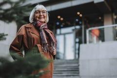 Frohe ältere Frau in den Gläsern, die auf der Straße aufwerfen lizenzfreie stockfotos