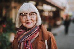 Frohe ältere Frau in den Gläsern, die draußen aufwerfen lizenzfreie stockfotos