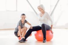 Frohe ältere Frau, die auf dem Eignungsball sitzt Stockfoto