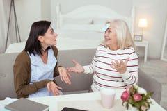 Frohe ältere Frau und Pflegekraft, die Charakter schätzt stockfoto