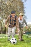 Frohe ältere Freunde, die Fußball in einem Park spielen Stockfoto