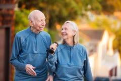 Frohe ältere Paare, die draußen gehen stockbilder
