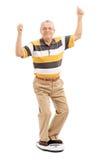 Frohe ältere Stellung auf einer Gewichtsskala Stockbild
