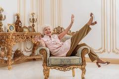 Frohe alte Dame, die zu Hause Luxus genießt lizenzfreies stockbild