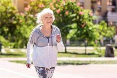 Frohe alte hübsche Frau, die Morgenübung tut lizenzfreies stockbild