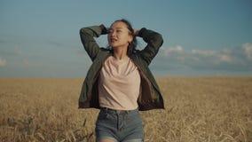 Frohe asiatische Frau, die auf dem Weizengebiet bei Sonnenuntergang geht stock footage