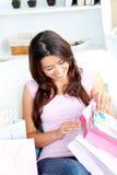 Frohe asiatische Frau mit Einkaufenbeuteln auf dem Sofa Stockbild