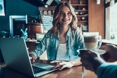 Frohe attraktive Frau grast Internet in der Kaffeestube Lizenzfreie Stockfotos