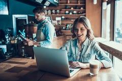 Frohe attraktive Frau grast Internet in der Kaffeestube Stockfotos