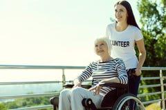 Frohe behinderte weibliche Person, die in ihrem Rollstuhl sitzt stockfotografie