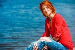 Frohe bequem sitzende und lächelnde Rothaarigefrau lizenzfreie stockfotos