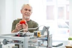 Frohe bewundern rote Tomate des älteren Mannes druckte mit Drucker 3D lizenzfreie stockbilder