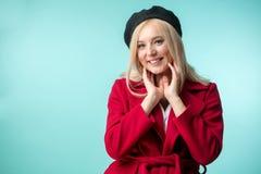 Frohe blonde Dame in der modernen Kleidung, die ihr Gesicht berührt Lizenzfreie Stockfotos